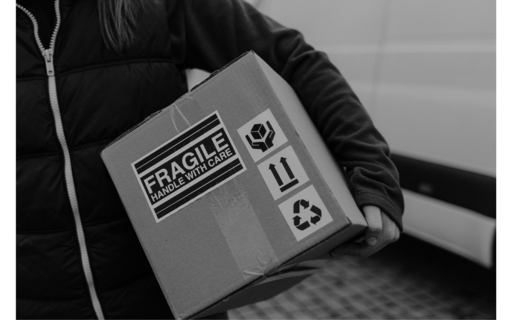 woman carrying cardboard box containing fragile items