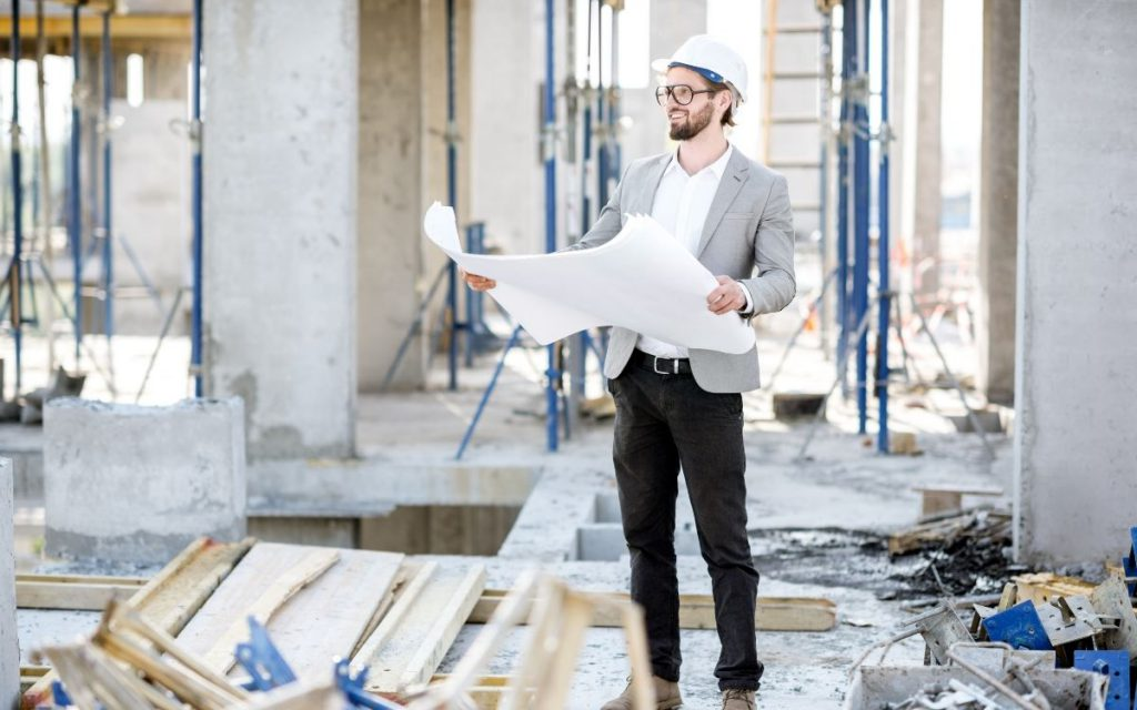 man in blazer and hard hat standing amongst construction holding plans